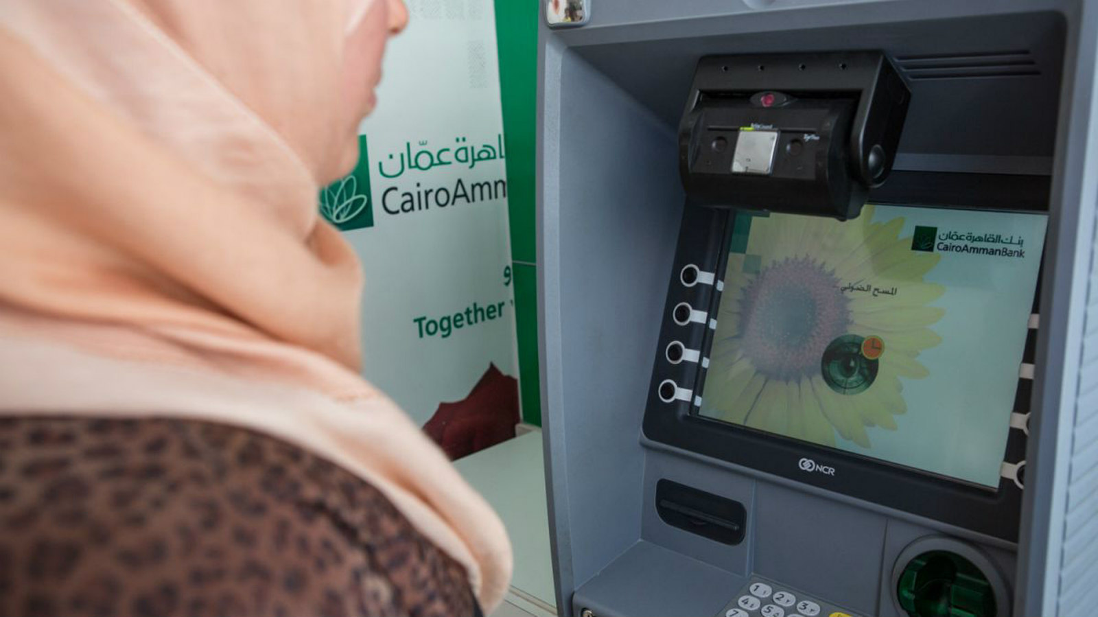 Syrian refugee at an ATM in Jordan (UNHRC.org)