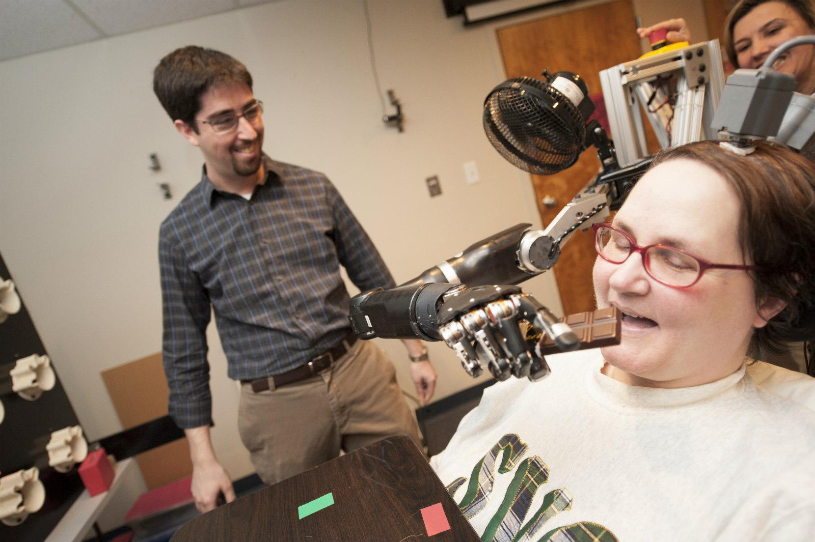 A Quadriplegic woman controlling a robotic arm in three dimensions through a BCI, UPMC, 2012.
